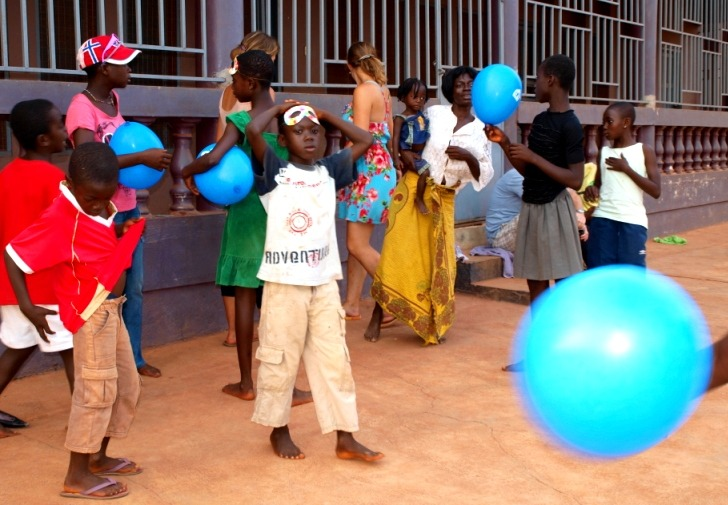Ghanaian children playing a game with a white volunteer