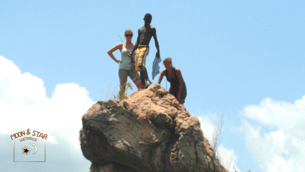 3 people on thelion rock at Bomfobiri park in Ashanti Ghana