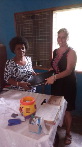 Pat handing over a laptop to one of the projects we support